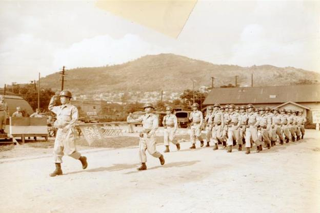 KATUSA soldiers marching in file (1955) (present-day Camp Coiner with Namsan Mountain in the background; ca. 1950s)